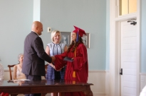 Sarah receives her diploma from Dr. Gates as President of the Board Joyce Gates looks on